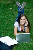 Cute teen girl laying down on the grass studying