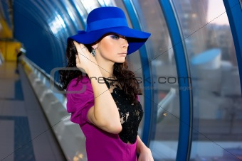 Beautiful girl in purple dress and blue hat