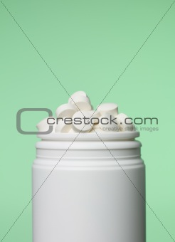 Can of pills toward green background