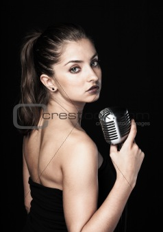 Beautiful woman holding retro microphone on black background