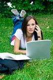 Cute teen girl on the phone laying down on the grass studying