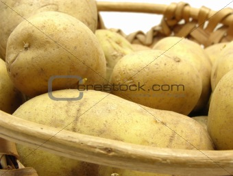 A basket with potatoes on a white background