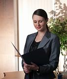 Young attractive business woman with folder