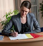 Young attractive business woman writing