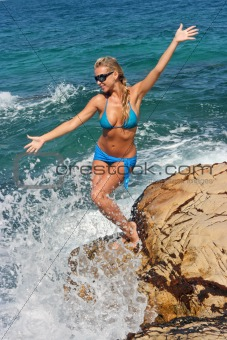 Blonde on rocky beach