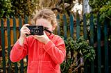 young girl in red jacket with camera