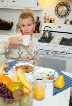 Attractive Woman In Kitchen with Fruit, Coffee, Orange Juice and Breakfast Bowls.