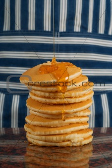 Pouring syrup on flapjacks