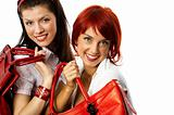 two young smiling caucasian women with red handbags
