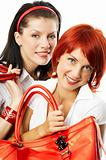 two young smiling women with red handbags