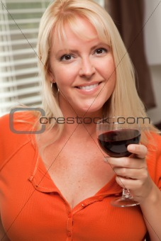 Attractive Blond with a Glass of Wine in the Kitchen
