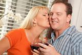 Happy Couple Enjoying a Glass of Wine the Kitchen.