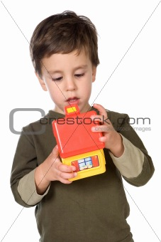 Adorable boy playing with a yellow house
