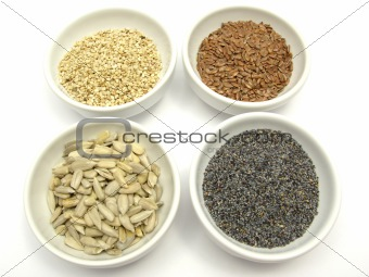 Four bowl with different seeds on a white background