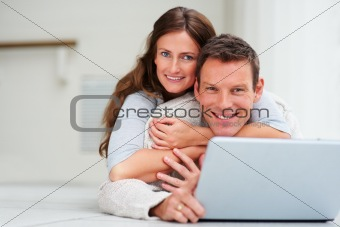 Happy and cheerful  young couple cuddling on the floor while using a laptop