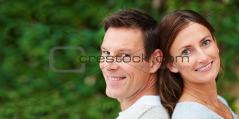 Portrait of a  happy and cheerful young couple with their backs together