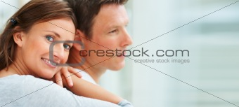 Closeup of a young beautiful woman embracing a man from behind