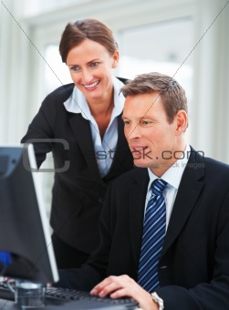 Portrait of confident successful business people working on computer together