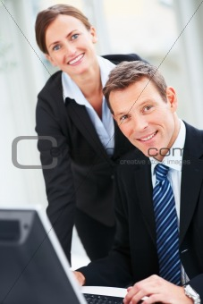 Portrait of happy and successful business people working on computer together