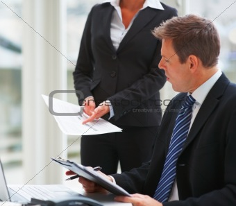 Closeup of business man reading paper held by colleague at work