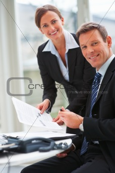 Portrait of a colleague holding paper to be signed by business man