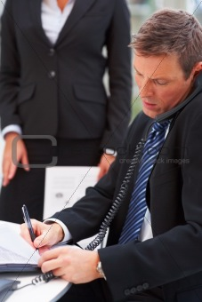 Portrait of business man speaking on phone and writing while colleague standing behind