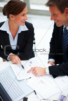 Portrait of happy business colleagues discussing over paper work