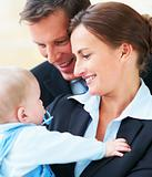 Closeup portrait of business couple holding their baby together