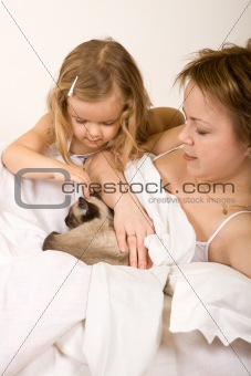 Little girl and her mother in bed with a kitten