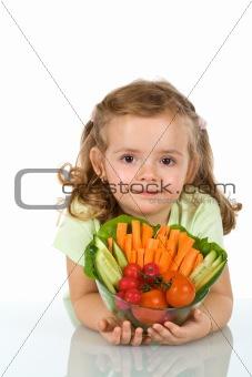 Little girl holding a bowl of vegetables