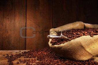 Burlap sack of coffee beans against dark wood