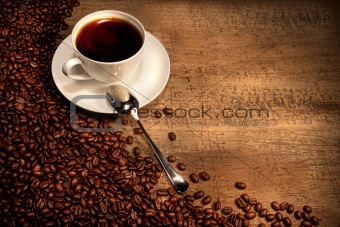 White coffee cup with beans on rustic table