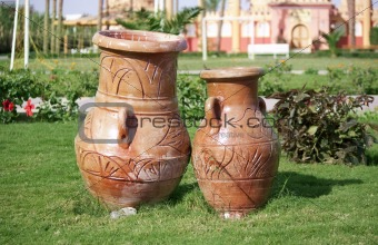 Old clay jugs on green field