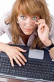 The tired young woman in glasses sits with the laptop. Isolated