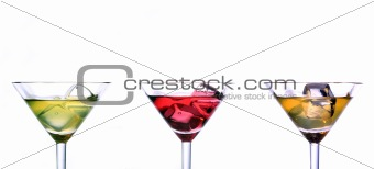 Three martini glasses with multicolor cocktails