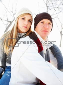 Portrait of a young couple sitting outdoors during winter season