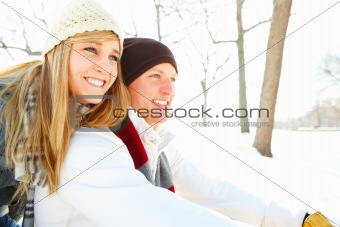 Closeup of a happy and excited young couple sitting outdoors during winter season