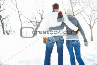 Rear view image of a young couple standing and holding each other outside during winter season