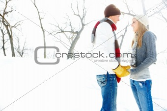 Closeup of a happy young couple holding each others hands and standing on snow