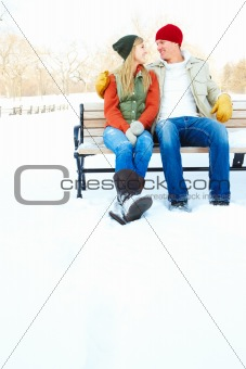 Portrait of a happy young couple sitting together on a bench during winter season