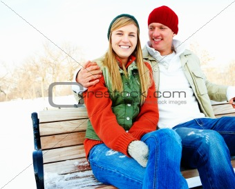 Portrait of a attracive young couple sitting on a bench outdoors during winter season