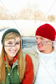 Portrait of a cheerful young couple sitting outside on a bench during winter season