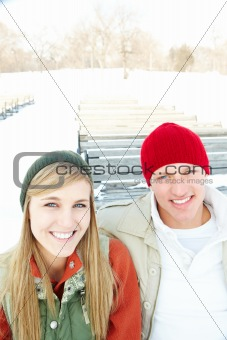 Portrait of a happy and cheerful young couple sitting outside