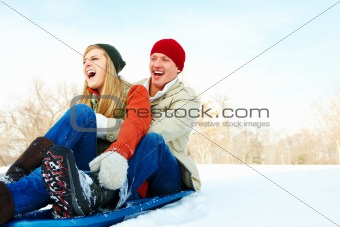 Portrait of a young couple on a snow sledge and sliding