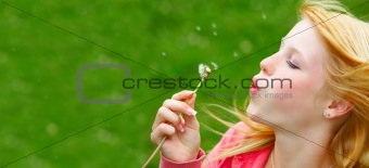 Young girl blowing seeds of a dandelion flower