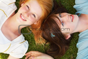 Pretty young girls lying together in fresh grass