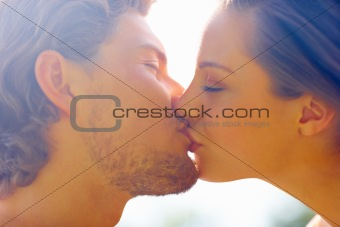 Closeup portrait of a romantic happy young couple kissing with eyes closed
