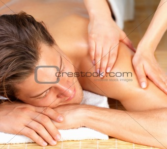 Young smart male enjoying massage with smile on his face