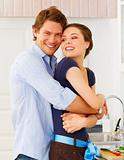 Lovely romantic couple in casuals enjoying a goodtime in kitchen