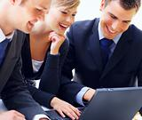 Smiling business people using a laptop during a meeting